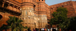 A crowd of people entering the Agra Fort through a gate in its massive walls.