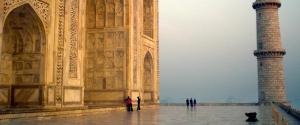 A man praying in front of the Taj Mahal at sunrise.